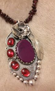 Purple bead chained necklace with silver pendant featuring flower, feather, red and purple stones by don gesaman